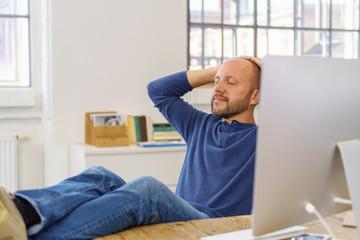 mann sitzt am schreibtisch und entspannt mit geschlossenen augen