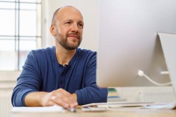 mann schaut lächelnd auf seinen computer