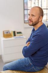 mann sitzt entspannt im büro auf dem tisch und schaut zur seite