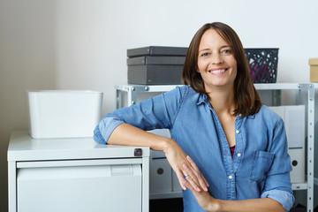 frau steht lächelnd in ihrem büro