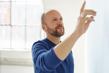 mann steht in der wohnung und zeigt mit der hand auf etwas