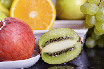 Fresh juicy cut kiwi fruit surrounded by colorful fruits