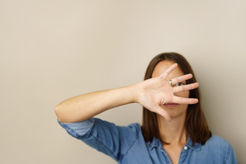 frau hält die hand vor ihr gesicht