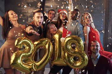 New 2018 Year is coming! Group of cheerful young multiethnic people in Santa hats carrying gold colored numbers and throwing confetti on the party