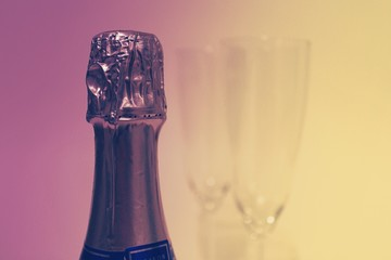 Purple and Yellow Color Champagne Bottle with Two Glasses in the Background