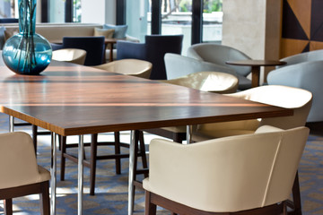 Working interior. Light leather chairs and brown wooden table.
