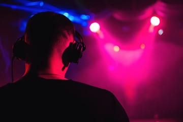 head DJ headphones from back closeup of musical event