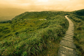 Fantasy-like landscape and path of stepping stones over a grassy bald on Taiwan's mountainous east coast