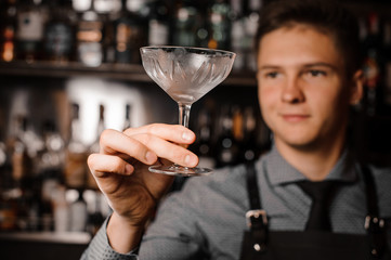 Young male barman holding a clear cocktail glass