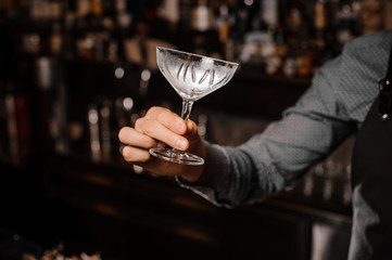 Barman hand holding an empty cocktail glass