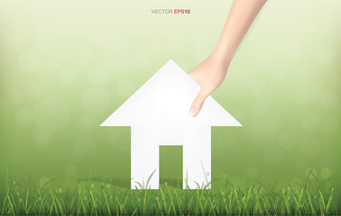 Hand pick a paper house on green yard area. Conceptual image of real estate idea. Vector illustration.