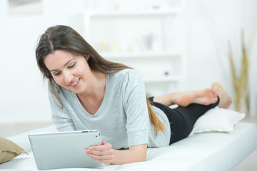 attractive young girl laying on bed holding a tablet