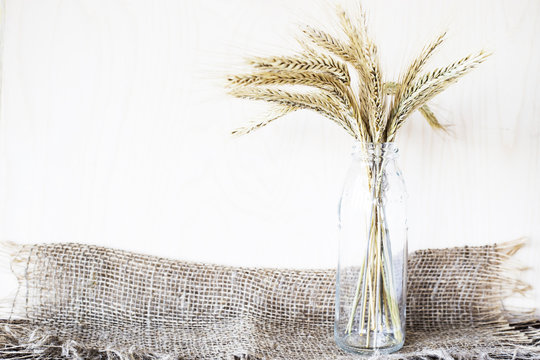 The concept of harvest. A bunch of rye and wheat in a glass pile on a table with burlap