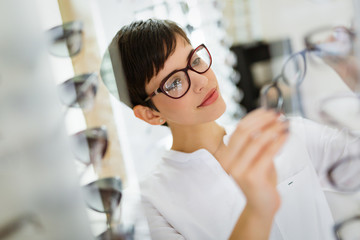 Pretty young woman is choosing new glasses at optics store Wall mural