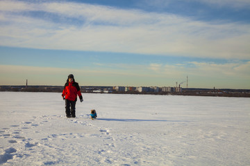 Boy and dog walking in winter.