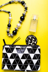 Woman handbag with makeup and accessories on yellow background. Flat lay...