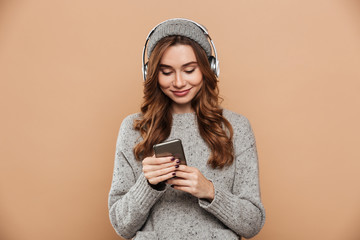 Portrait of young attractive woman in gray hat and sweater using mobile phone while listening to music