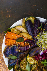 Baked and raw vegetables with herbs served on white plate.