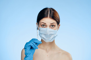 Beautiful young woman on a blue background holds syringes, medicine, plastic