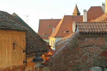 Old traditional romanian vintage orange brown houses with dormers attic windows designed in eyes shape at tile roofs in the evening at city center.