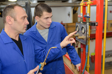 modern industrial machine operator working with apprentice