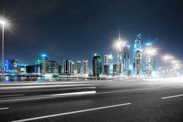 Fotomurales - empty asphalt road with modern buildings at night