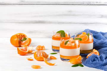 Creamy panna cotta with orange jelly in beautiful glasses, fresh ripe mandarin, blue textile on white wooden background. Delicious Italian dessert. Closeup photography.Selective focus.