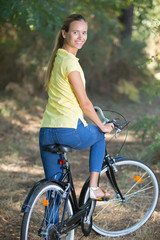 young woman biking in the forest