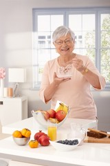 Happy granny eating breakfast cereal