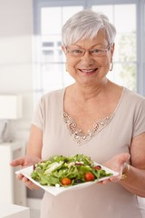 Happy old lady holding fresh green salad