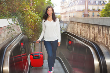 Beautiful woman with suitcase going up escalator