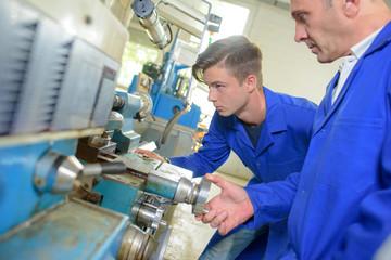 Supervisor watching apprentice engineer
