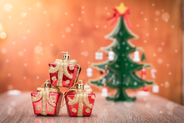 The abstract image of the small gift boxes on the table and the christmas tree is backdrop during snowing. the concept of festival, business, sales, gift, new year and christmas.