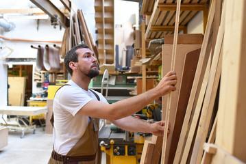 Tischler am Arbeitsplatz in einer Schreinerei // Joiner at the workplace in a carpenter's workshop
