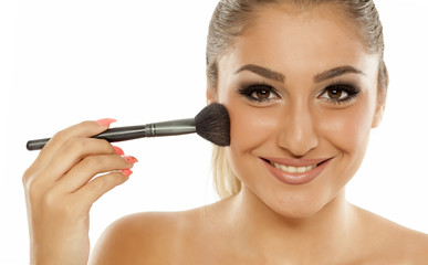 young beautiful woman applied blush with a brush