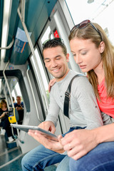 Couple on public transport, looking at tablet