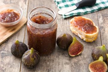 Sweet fig jam in jar on wooden table