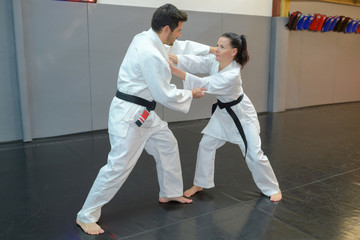 woman and man judo fighters in sport hall