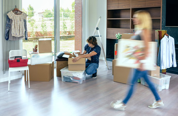 Young woman carrying painting while her husband unpacks