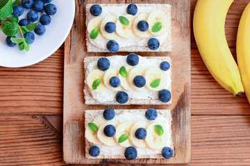 Soft cheese cream, bananas, mint and berries sandwiches. Vegetarian diet sandwiches crispbread on wooden board. Top view