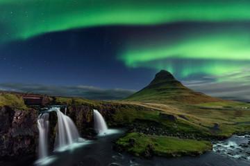 Aurora boreal sobre surpreendente paisagem Islandesa com o monte Kirkjufell em segundo plano.