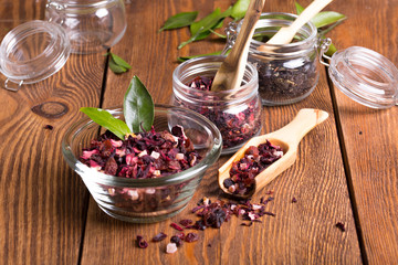 Herbal aroma fruit tea dry leaves on spoon on wooden background