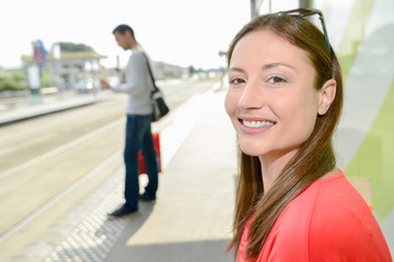 Radiant young woman waiting on a platform