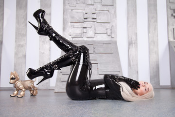 Beautiful Long Hair Blond Woman Wearing Black Tight Latex Costume Playing With Her Dog Robot On The Floor of Space Ship