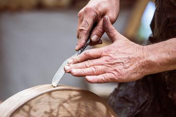 Mann schärft Messer mit dem Schleifstein