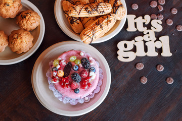 Sweet cheese cake with fresh berries and yoghurt cream and wooden sign Its A Girl. Baby shower party sweets.