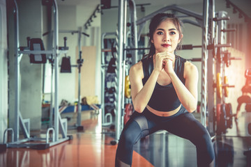 Young Asian woman doing squat workout for fat burning and diet in fitness sports gym with sports equipment in background. Beauty and body build up concept. Sports club and Aerobic theme.