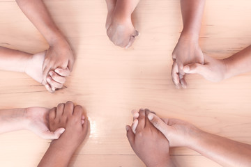 Topview of parent and children holding hands and praying together on wooden table