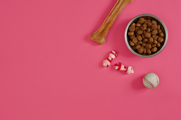 Dog snacks, dog chews, dog bone, ball toy for dog on a pink background with copy space