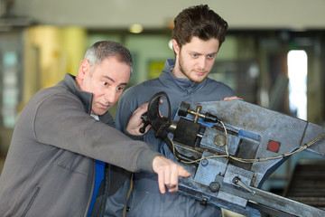 impatient man pointing where apprentice needs to direct machine